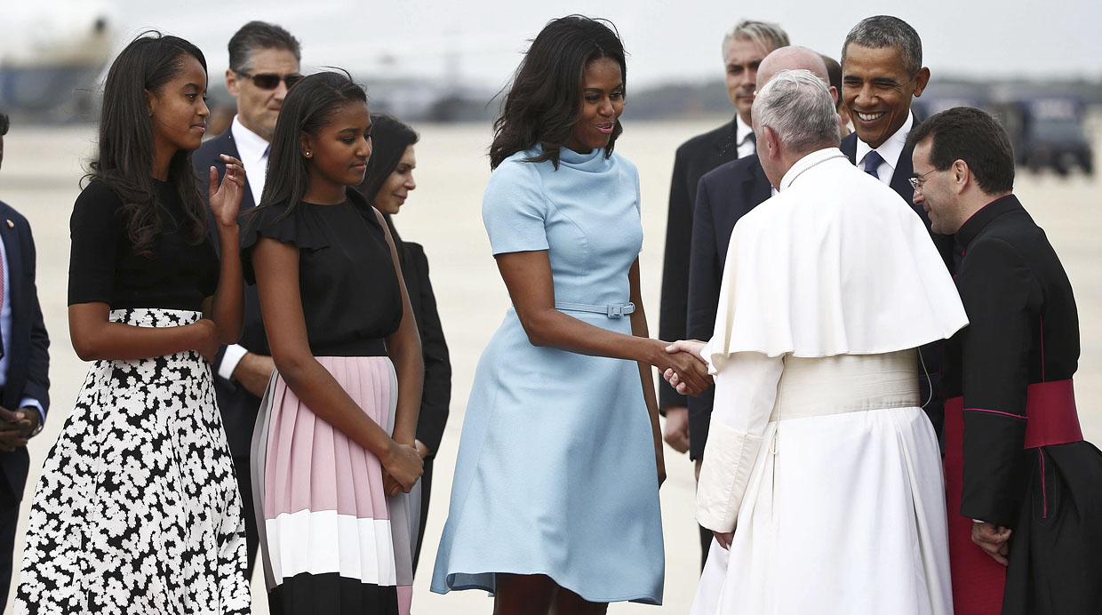 U.S. President Barack Obama (R) smiles as Pope Francis shakes hands with first lady Michelle Obama as the Obama's daughters Malia (L) and Sasha look on upon his arrival at Joint Base Andrews outside Washington September 22, 2015.    REUTERS/Tony Gentile