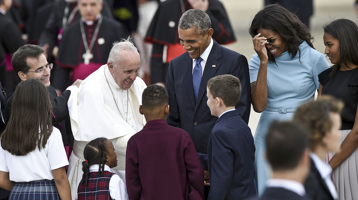 Pope Francis greets people as he is escorted by President Barack Obama after arriving at Andrews Air Force Base in Md., Tuesday, Sept. 22, 2015. The Pope is spending three days in Washington before heading to New York and Philadelphia. This is the Pope's first visit to the United States. First lady Michelle Obama, second from right, and Sasha Obama, right, watch. (AP Photo/Susan Walsh)