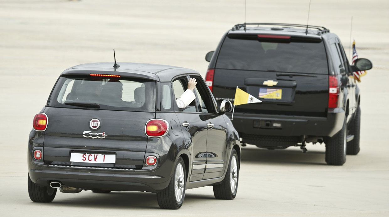 Pope Francis waves as he departs Joint Base Andrews, Maryland in a Fiat 500 (L) after arriving for his first trip to the U.S. September 22, 2015.  A U.S. Secret Service Chevrolet Suburban leads the Pope's vehicle.    REUTERS/Kevin Lamarque